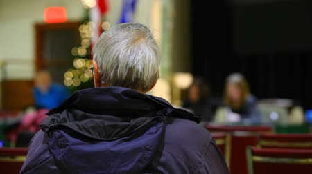 origens : wearing a winter coat sitting on a chair and listening to an official speech with blurry background seen from behind - fixed angle Vídeos