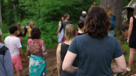 divinity : A mixed group of people are seen from behind, practicing deep breathing exercises during a mindful nature retreat seeking spirituality and enlightenment.
