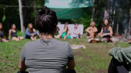 divinity : A young woman is shot in slow-mo from the rear, as a blurry spiritual guide is seen in the background teaching alternative healing techniques in nature. Stock Footage