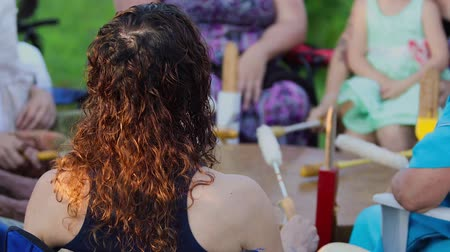 native american culture : A short clip shot close up on the back of a womans head with frizzy red hair, sat in a circle with a group of people all playing a mother drum together. Stock Footage