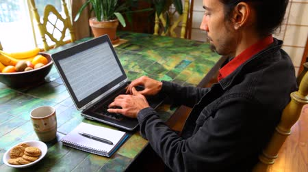 Young man wearing a black jacket and a red shirt is typing on a black laptop in his dining room. Traveling up from the left. Portrait view Stock Footage