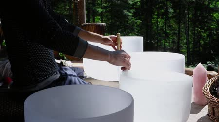 shaman : A shamanic guide is seen playing quartz singing dishes during a woodland retreat where people experience native and traditional cultures, slow motion footage.