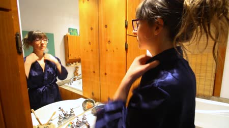 without face : Young woman with glasses is looking at her reflection in the bathroom mirror and placing the collar of her dressing gown - fixed angle