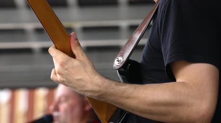 canadense : Closeup and slow motion footage of a male guitarist playing with an indigenous band on stage, details of the leather shoulder strap and wooden instrument.