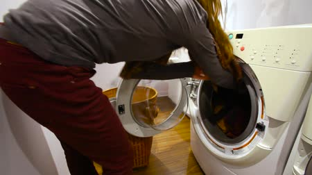 housekeeper : Young woman is putting dirty laundry in the washing machine in the utility room - traveling up