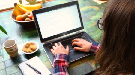 authenticity : Girl wearing glasses and a checkered shirt is typing on her black keyboard with coffee and cookies by her side. Fixed angle from the top left Stock Footage
