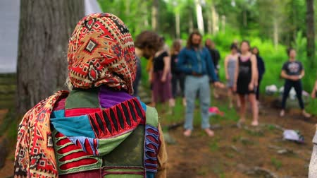 shaman : Slow motion camera panning on the back of person wearing brightly colored clothes and scarf, standing in a circle with a mixed group of people in a forest.