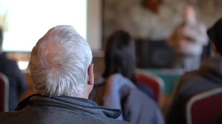 inventor : Closeup shot on the back of an elderly mans head during a presentation for environmentally friendly waste management solution. Blurry talker seen in background Stock Footage