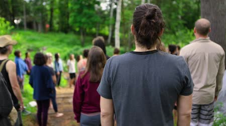 divinity : A young caucasian person is viewed from behind, wearing a grey t-shirt with hair tied up, standing in a forest clearing with a mixed group during mindful prayer