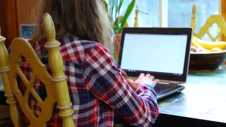 Girl with glasses is wearing a checkered shirt, typing on a 15 inches black laptop. Closeup fixed angle from the back