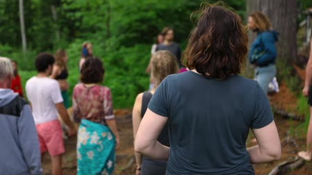 divinity : A closeup and rear view on the back of a caucasian person practicing deep breathing exercise amongst an intergenerational group of people at a woodland retreat. Stock Footage