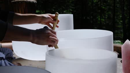 divinity : A short slow motion clip on the hands of a spiritual guide using crystal singing bowls to create healing sounds during a multicultural celebration in nature.