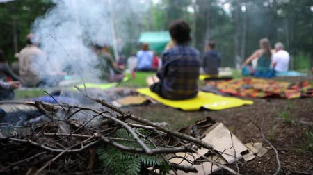divinity : Rising smoke from kindling on a camp fire is seen close up in slow motion, setting the calm atmosphere during a group meditation and yoga session in nature.