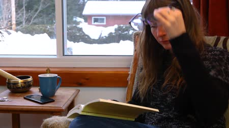 konfor : Young woman with wooly grey shirt puts on her glasses while reading a book surrounded by windows. Traveling up