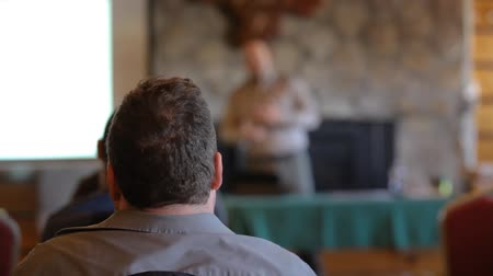 inventor : An overweight man with brown hair is seen from the rear during a meeting about innovative new ecological waste products. Blurred speaker is seen in background.