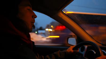 Young man with long hair is driving through his small city at night. Blurred lights in the background. Fixed wide angle scene