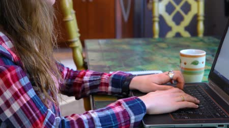 freelance work : Girl with glasses wearing a checkered shirt is typing on her keyboard. Travelling up closeup scene