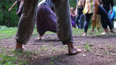 istenség : A large group of barefooted people are seen freely moving their bodies during a dance routine to reach a tranquil and enlightened state during native festival. Stock mozgókép