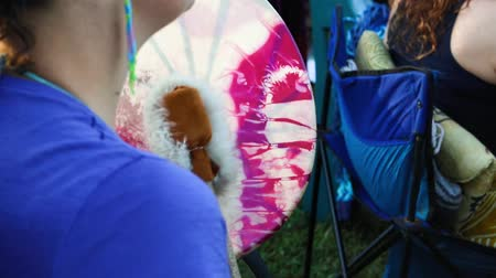 nativo americano : Closeup and slow motion footage seen over the shoulder of a drummer, using a colorful native drum and fur lined leather beater as people celebrate ancient culture