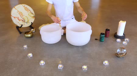 singing bowl : Fixed angle scene of a young man dressed in white, sitting in indian surrounded by instruments and playing his two crystal bowls as part of a meditative concert Stock Footage