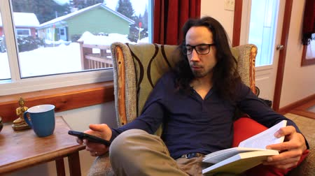 уведомление : Young man with long hair, reading glasses and cozy clothes is checking the notification of his mobile phone while reading a book. Surrounded by windows at home. Fixed angle Стоковые видеозаписи