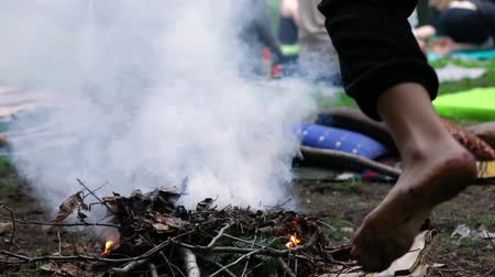 divinity : A closeup and slow motion clip of a barefooted person placing kindling on a smoking campfire as blurred people are seen meditating in the background.