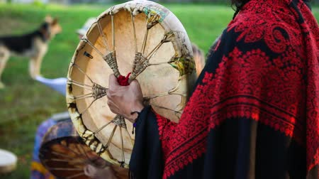 nativo americano : Close up and slow-mo footage of a shaman creating acoustic sounds with a native rawhide drum, wearing colorful clothes in a park during a music celebration. Stock Footage