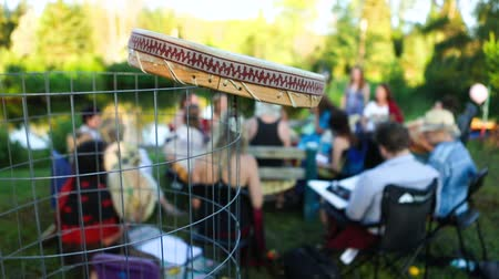 native american culture : Blurred people are seen in a singing circle at a local park during a sunny afternoon, details on the side of a handmade native drum are seen in the foreground. Stock Footage