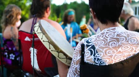 shaman : Slow motion footage of a native singing circle in an outdoor park, shot over the shoulder of a woman with short hair playing a handcrafted drum.