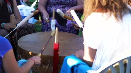 Closeup and slow motion footage on a group of people beating a mother drum in unison during a shamanic powwow, seeking mindfulness and spirituality through music.