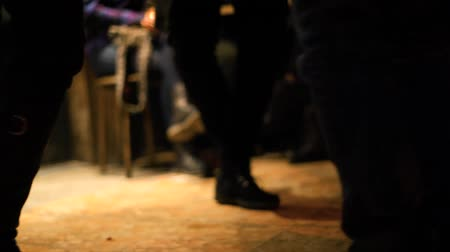 гитара : A ground level view on the feet of a group of people dancing and tapping feet on the wooden floor of a public house by night.