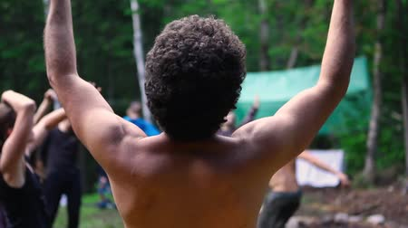 divinity : A closeup and rear view of a muscular shirtless man with afro style hair, enjoying qigong dance in nature, used to balance sacred chi (life force energy).