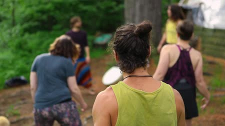 divinity : A closeup and rear view of a healthy young man, seen in slow motion as free spirited people dance and move their bodies in the woods during a mindful retreat.