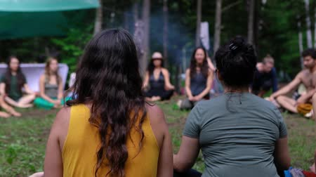 A large group of people are seen sitting around a spiritual guide in a forest clearing as she teaches deep and mindful meditation at multicultural festival.