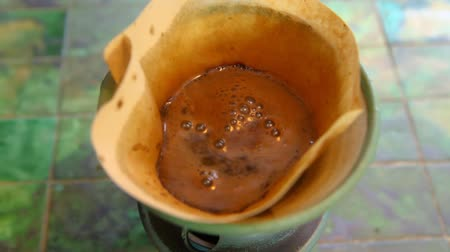 rögzített : Pouring boiling water on coffee grain in a ceramic filter holder. Fixed angle from the top