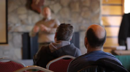 ambientalmente : Atmosphere inside a meeting room as a guy is seen giving a ecological presentation blurry in the background, two men are seen sitting from the back. Stock Footage