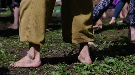 divinity : A closeup view on the bare feet of a group of people as they enjoy chi kung dance, slow moving free dance style used in alternative healing and meditation.