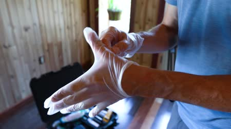 impactor : A closeup view on the muscular arms of a building surveyor at work, struggling to fit single use gloves over large hands, preparing for home inspection.