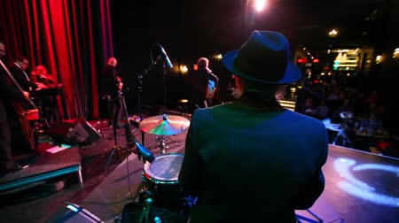 felvonás : View from behind a drummer of a folk music group as they entertain fans inside a nightclub. Bandmembers and audience are seen blurry in the background.
