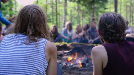divinity : A mixed group of people are seen in slow-mo, watching sacred objects thrown on to a burning fire in a forest clearing during a shamanism festival in nature.