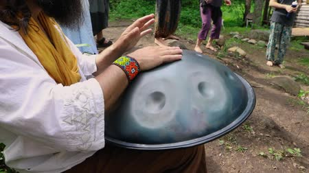 divinity : A shamanic musician is seen up close, playing a metal handpan drum with hands during a multicultural festival in a sacred forest clearing with barefooted people Stock Footage