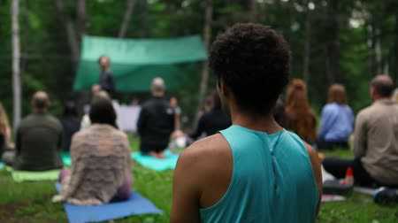 divinity : A healthy and slim thirty year old is viewed from the rear, as a group of multiethnic people practice mindful meditation during a retreat to nature.