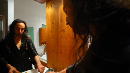 preventive : Man with long hair is looking at his reflection in the bathroom mirror and brushing his teeth - fixed angle Stock Footage
