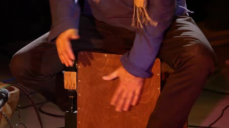 glied : A band member is viewed up close during a live music set in a night club, using hands to strike a wooden board as a percussion instrument.