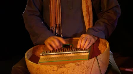 Close up and intimate footage of a skilled musician using fingers to play a small kalimba, an idiophone used in traditional African music.