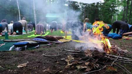 multikulturní : A flaming camp fire is seen up-close in slow motion, as people practice meditation and sacred yoga during a multicultural festival at a sacred forest clearing.