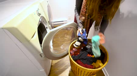 prát : Young woman is putting dirty laundry in the washing machine in the utility room - fixed angle