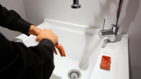 Wide view of man with long hair washing his hands with a red soap bar above a large white sink in the utility room - fixed angle