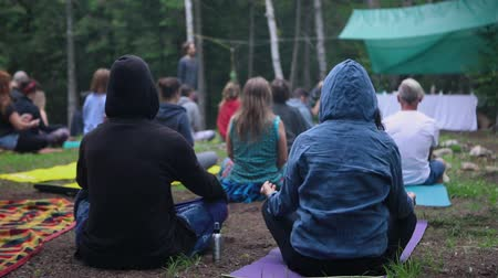 отступление : Mindful individuals are seen from behind in slow-mo, seeking enlightenment and contemplation during a woodland retreat dedicated to multicultural experiences.