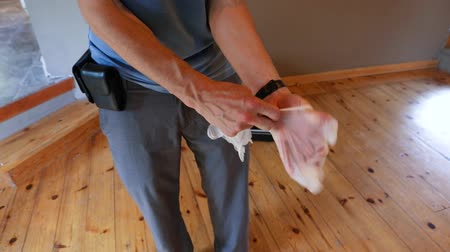 ventilazione : A short video shot up-close as a caucasian building inspector prepares for work, placing protective latex gloves on hands during a residential home checkup.